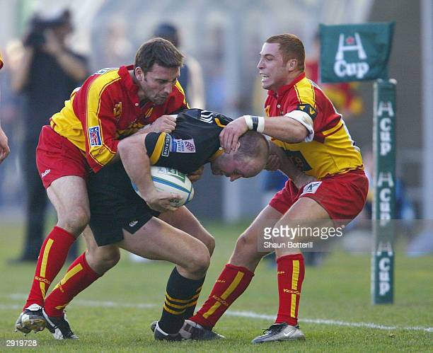 Alex King of Wasps is held up by Pascal Giordani and Pascal Bomati of Perginan during the Heineken Cup match between Perpignan and Wasps at the Aime...