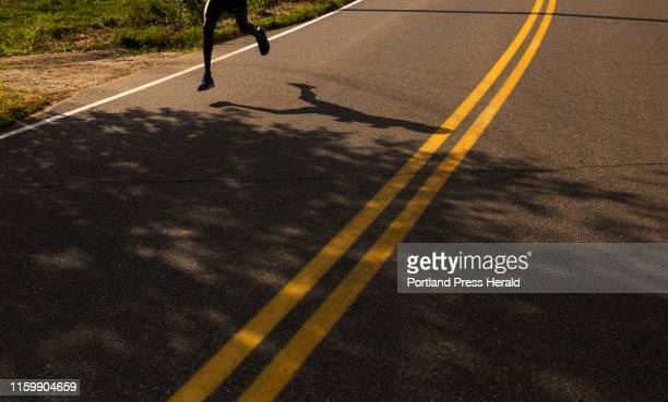Alex Korio's shadow as he runs on Shore Road in the annual Beach to Beacon on Saturday August 3 2019 Korio came in first place with a time of 2734