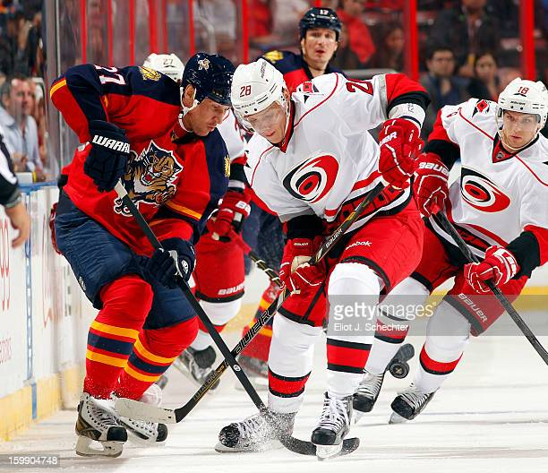 Alex Kovalev of the Florida Panthers crosses sticks with Alexander Semin of the Carolina Hurricanes at the BBT Center on January 19 2013 in Sunrise...