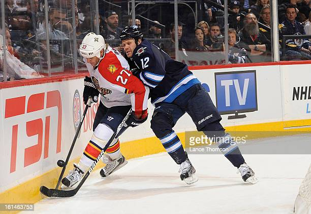 Alex Kovalev of the Florida Panthers guards the puck along the boards as Olli Jokinen of the Winnipeg Jets checks him during third period action at...