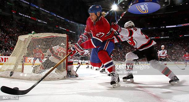 Alex Kovalev of the Montreal Canadiens carries the puck as he is checked by Patrik Elias of the New Jersey Devils during their NHL game at the Bell...