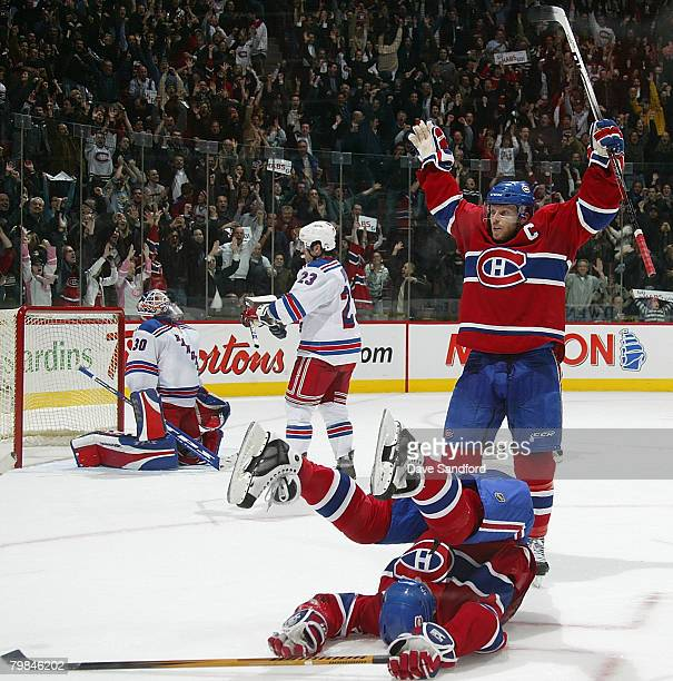 Alex Kovalev of the Montreal Canadiens lies on the ice as he celebrates his game tying goal with teammate Saku Koivu while Henrik Lundqvist of the...
