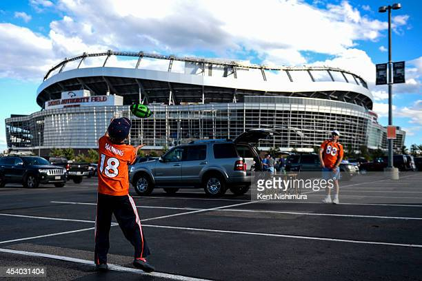 Alex Kubacki tosses a football with his father Michael Kubacki before the start of the a preseason football game between the Denver Broncos and the...