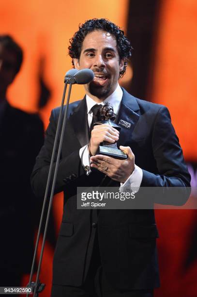 Alex Lacamoire receives the award for Oustanding Achievement In Music for 'Hamilton' on stage during The Olivier Awards with Mastercard at Royal...