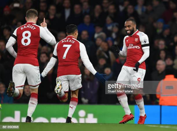 Alex Lacazette celebrates scoring for Arsenal with Alexis Sanchez and Aaron Ramsey during the Premier League match between Arsenal and Huddersfield...