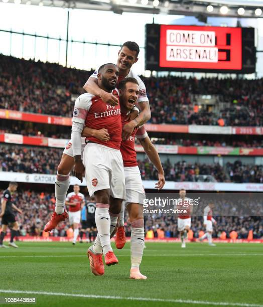 Alex Lacazette celebrates scoring the 1st Arsenal goal with Granit Xhaka and Aaron Ramsey during the Premier League match between Arsenal FC and...