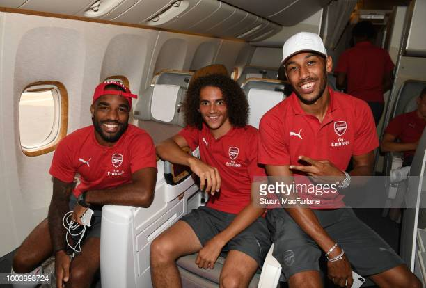 Alex Lacazette, Matteo Guendouzi and Pierre-Emerick Aubameyang of Arsenal pose on the team flight as they depart for the pre season tour to Singapore...