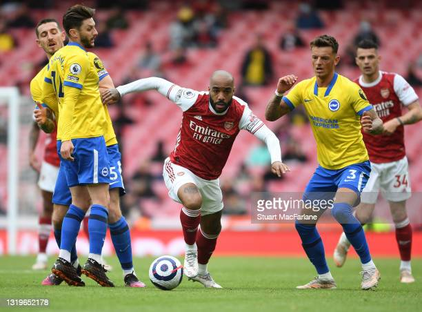 Alex Lacazette of Arsenal breaks past Adam Lallana and Ben White of Brighton during the Premier League match between Arsenal and Brighton & Hove...