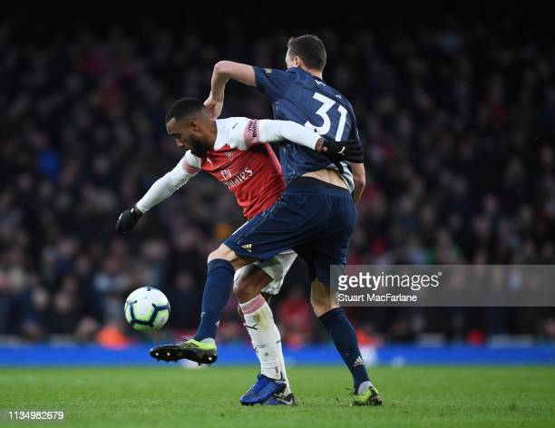 Alex Lacazette of Arsenal challenged by Nemanja Matic of Man United during the Premier League match between Arsenal FC and Manchester United at...