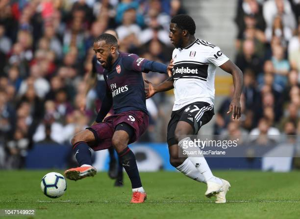 Alex Lacazette of Arsenal holds off Aboubakar Kamara of Fulham during the Premier League match between Fulham FC and Arsenal FC at Craven Cottage on...