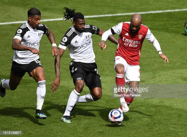 Alex Lacazette of Arsenal takes on Mario Lemina and Andre-Frank Zambo Anguissa of Fulham during the Premier League match between Arsenal and Fulham...