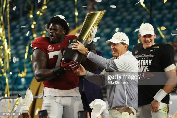 Alex Leatherwood of the Alabama Crimson Tide holds the trophy alongside head coach Nick Saban following the College Football Playoff National...