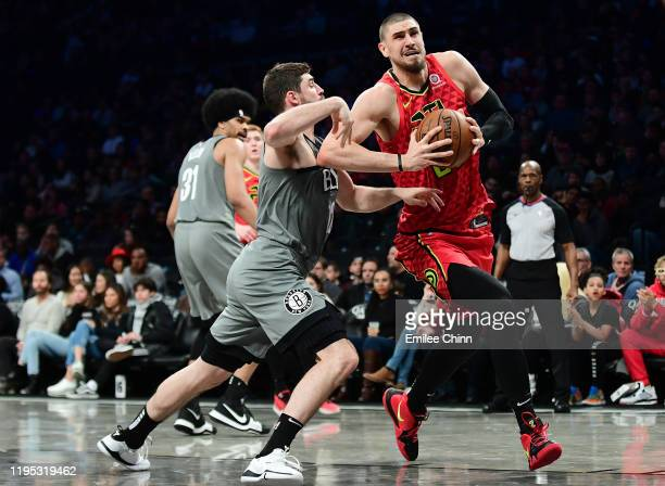 Alex Len of the Atlanta Hawks drives past Joe Harris of the Brooklyn Nets during the second half of their game at Barclays Center on December 21 2019...