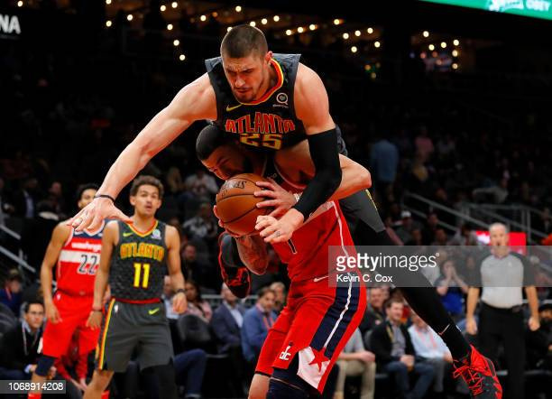Alex Len of the Atlanta Hawks is charged with a foul as he falls over top of Austin Rivers of the Washington Wizards at State Farm Arena on December...