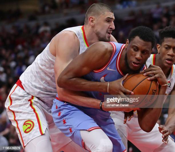Alex Len of the Atlanta Hawks pressures Thaddeus Young of the Chicago Bulls at the United Center on December 28 2019 in Chicago Illinois The Bulls...