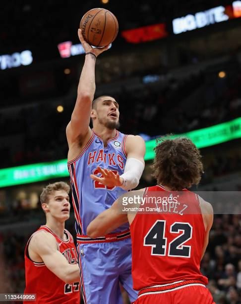 Alex Len of the Atlanta Hawks shoots between Lauri Markkanen and Robin Lopez of the Chicago Bulls at the United Center on March 03 2019 in Chicago...