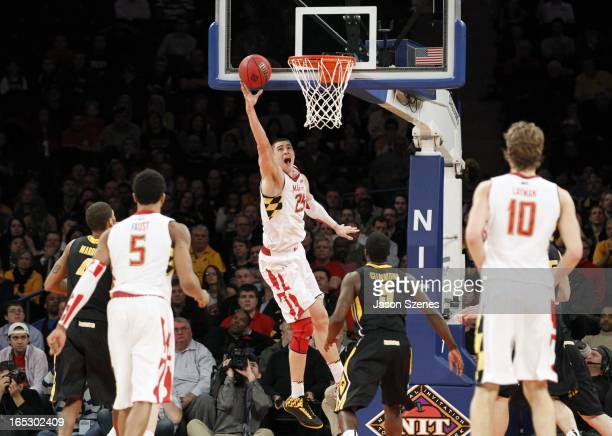 Alex Len of the Maryland Terapins puts up a basket past Anthony Clemmons of the Iowa Hawkeyes defense in the second half during the 2013 NIT...