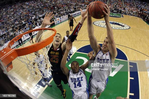 Alex Len of the Maryland Terrapins goes for a loose ball against teammates Mason Plumlee and Rasheed Sulaimon of the Duke Blue Devils during the...