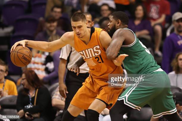 Alex Len of the Phoenix Suns handles the ball against Amir Johnson of the Boston Celtics during the NBA game at Talking Stick Resort Arena on March 5...