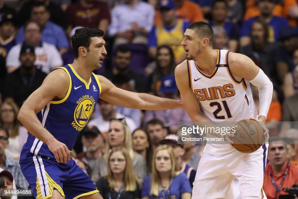 Alex Len of the Phoenix Suns handles the ball against Zaza Pachulia of the Golden State Warriors during the first half of the NBA game at Talking...