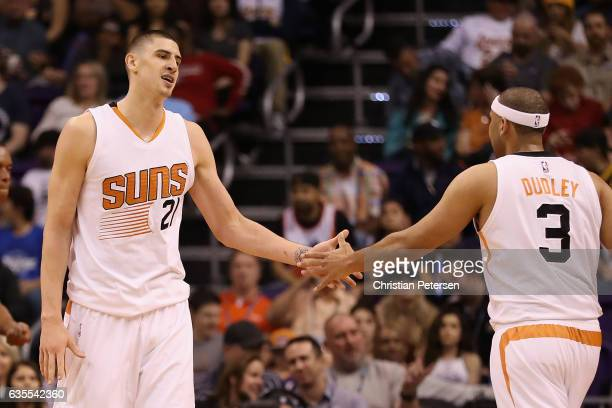 Alex Len of the Phoenix Suns high fives Jared Dudley after scoring against the Los Angeles Lakers during the first half of the NBA game at Talking...