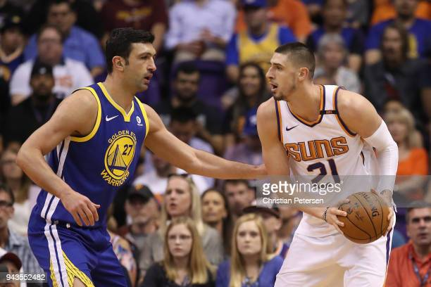 Alex Len of the Phoenix Suns looks to pass around Zaza Pachulia of the Golden State Warriors during the first half of the NBA game at Talking Stick...
