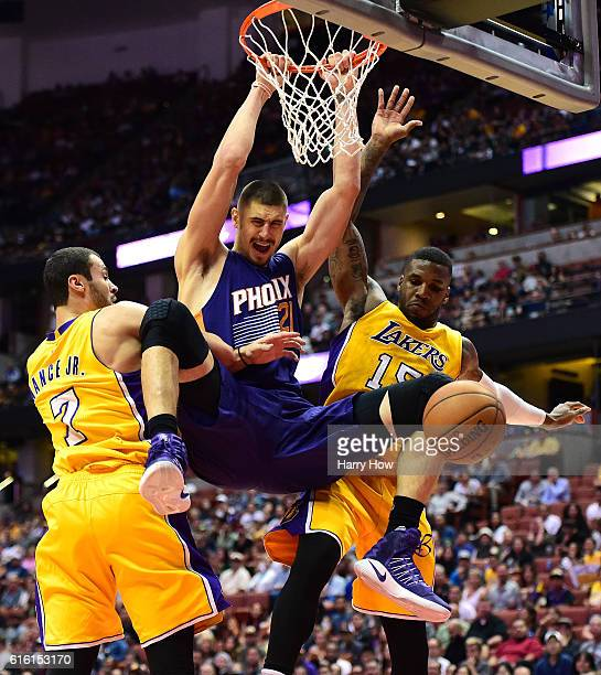 Alex Len of the Phoenix Suns reacts to his dunk between Larry Nance Jr #7 and Thomas Robinson of the Los Angeles Lakers during a 9894 Suns preseason...