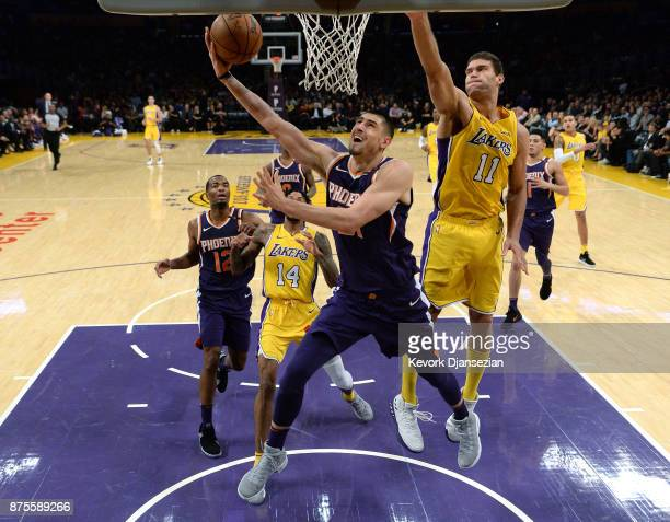 Alex Len of the Phoenix Suns scores basket against Brook Lopez of the Los Angeles Lakers during the second half of a basketball game at Staples...