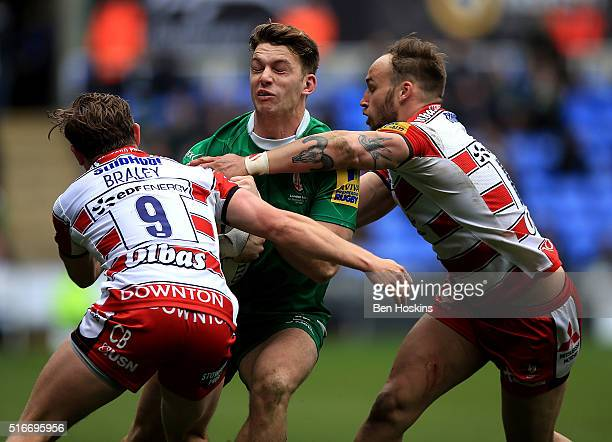 Alex Lewington of London Irish is tackled by Callum Braley and Bill Meakes of Gloucester during the Aviva Premiership match between London Irish and...