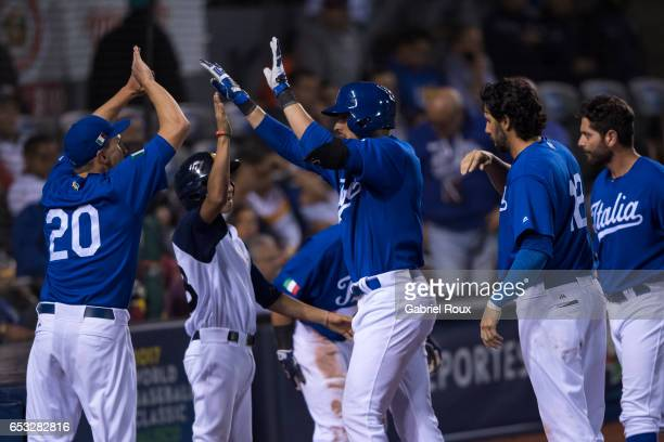 Alex Liddi of Team Italy is greeted by teammates at home plate after hitting a home run in the ninth inning during Game 6 of Pool D of the 2017 World...