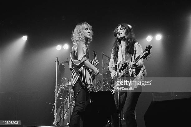 Alex Lifeson guitarist and Geddy Lee singer and bassist singing into a microphone on stage during a live concert performance by Canadian rock band...