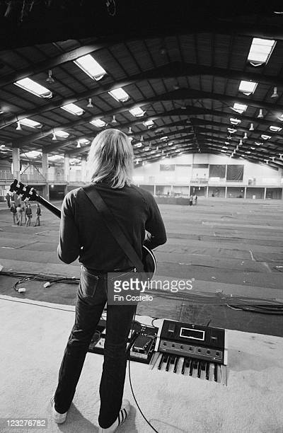 Alex Lifeson guitarist with Canadian rock band Rush viewed from behind as he plays his guitar to an empty arena during a soundcheck ahead of the...