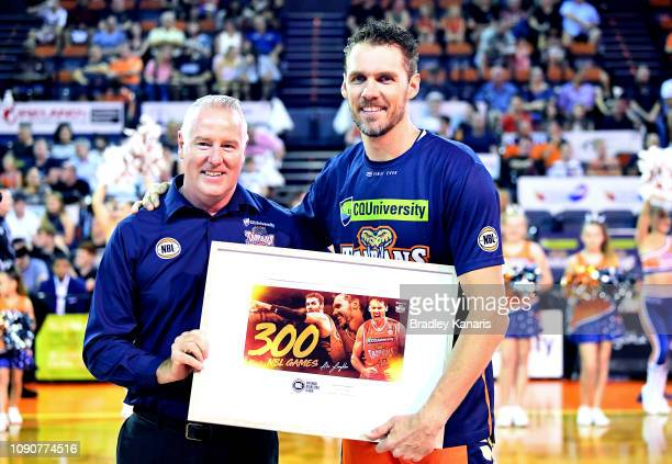Alex Loughton of the Taipans is presented with a print for his 300th NBL match with CEO Mark Beecroft before the round 12 NBL match between the...