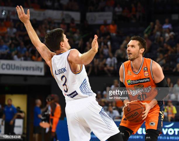 Alex Loughton of the Taipans looks to make a shot over Cameron Gliddon of the Bullets during the round 12 NBL match between the Cairns Taipans and...