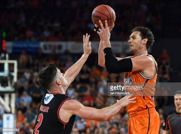 Alex Loughton of the Taipans looks to pass the ball over Lucas Walker of the Wildcats during the round 12 NBL match between the Cairns Taipans and...