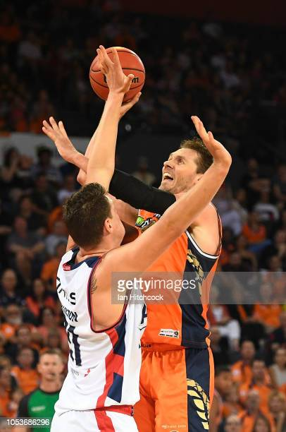 Alex Loughton of the Taipans takes a shot over Daniel Johnson of the 36ers during the round three NBL match between the Cairns Taipans and the...