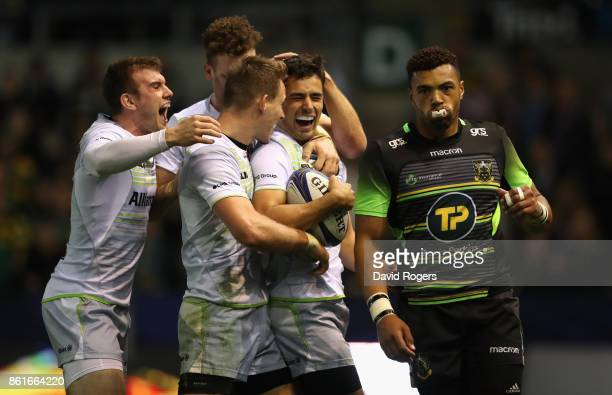 Alex Lozowski of Saracens is mobbed by team mates after scoring a try as Luther Burrell looks dejected during the European Rugby Champions Cup match...