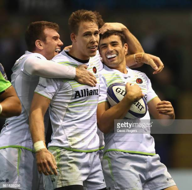 Alex Lozowski of Saracens is mobbed by team mates after scoring a try during the European Rugby Champions Cup match between Northampton Saints and...