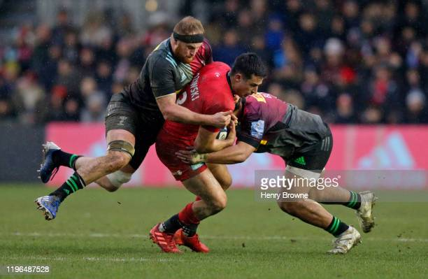 Alex Lozowski of Saracens is tackled by James Chisholm and Elia Elia of Harlequins during the Gallagher Premiership Rugby match between Harlequins...