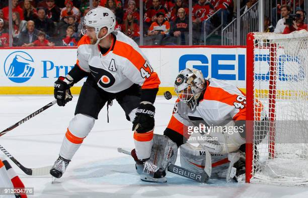 Alex Lyon and Andrew MacDonald of the Philadelphia Flyers defend the net in the second period against the New Jersey Devils on February 1 2018 at...