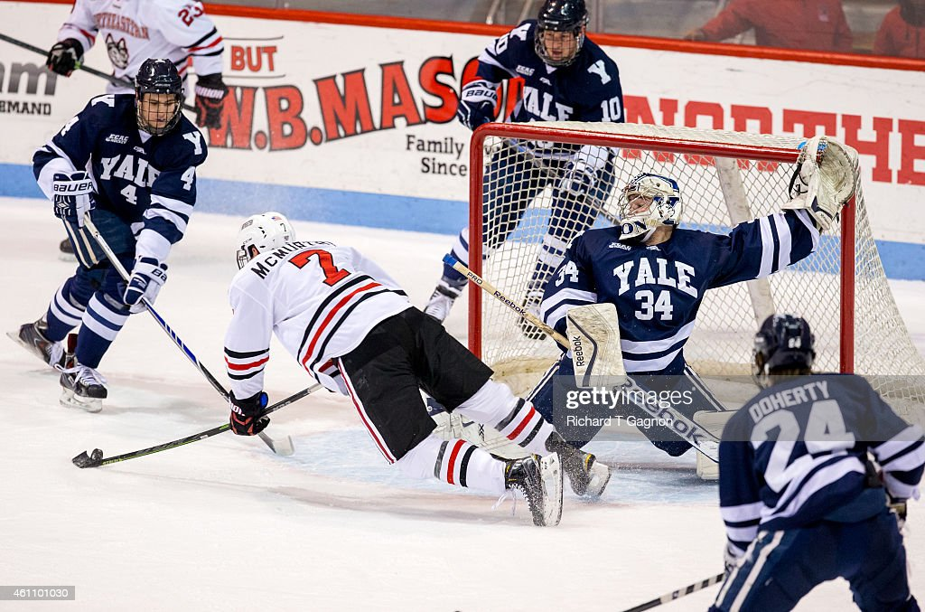 Alex Lyon #34 of the Yale Bulldogs makes a save against Mike McMurtry #7 of the Northeastern Huskies during NCAA hockey at Matthews Arena on January 6, 2015 in Boston, Massachusetts.