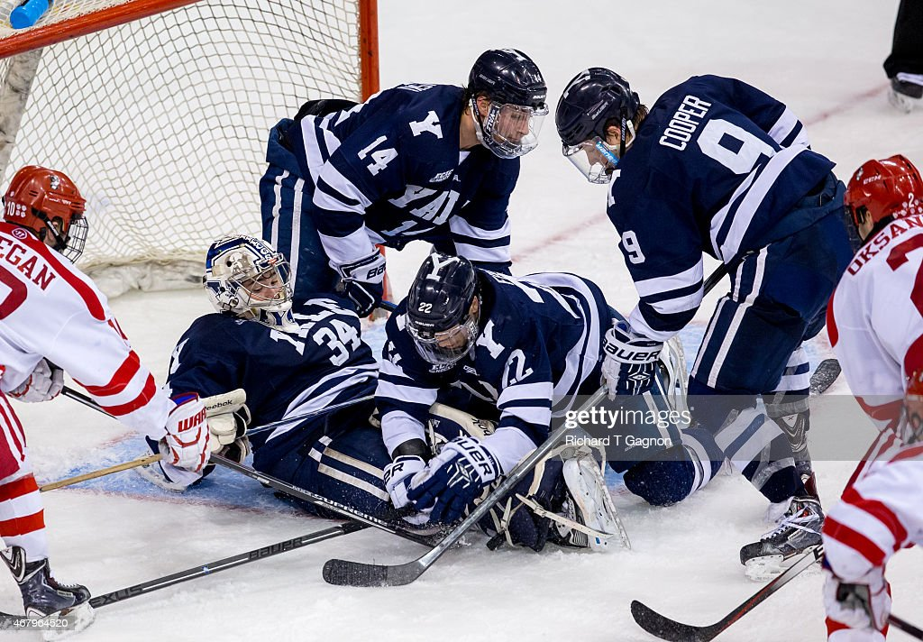 Alex Lyon #34 of the Yale Bulldogs makes a save against the Boston University Terriers as teammates Ryan Obuchowski #14, Carson Cooper #9 and Tommy Fallen #22 battle in the crease during the NCAA Division I Men's Ice Hockey Northeast Regional Championship Semifinal at the Verizon Wireless Arena on March 27, 2015 in Manchester, New Hampshire.