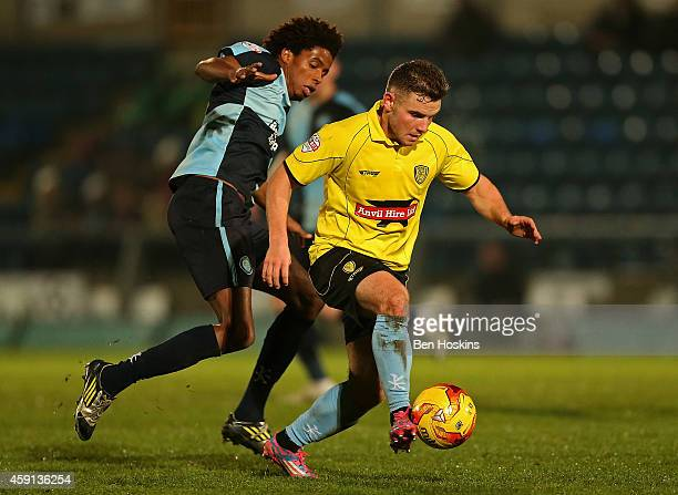 Alex MacDonald of Burton holds off pressure from Sido Jombati of Wycombe during the Sky Bet League Two match between Wycombe Wanderers and Burton...