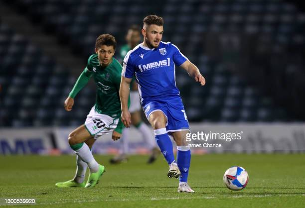 Alex MacDonald of Gillingham FC passes the ball under pressure from Brennan Johnson of Lincoln City during the Sky Bet League One match between...