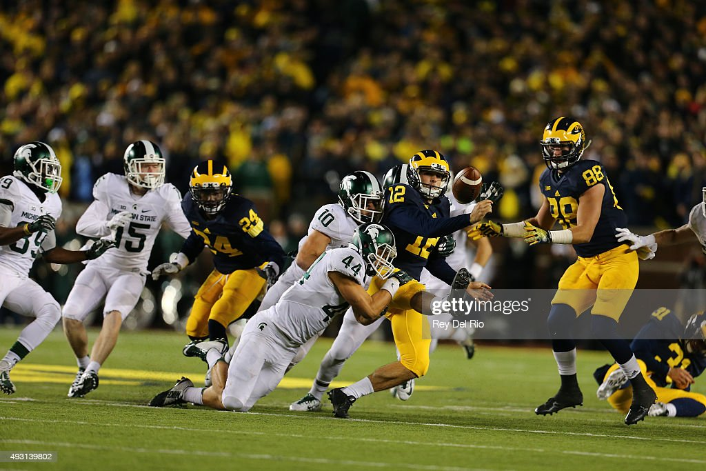 Alex Malzone #12 of the Michigan Wolverines fumbles late in the fourth quarter at Michigan Stadium on October 17, 2015 in East Lansing, Michigan.