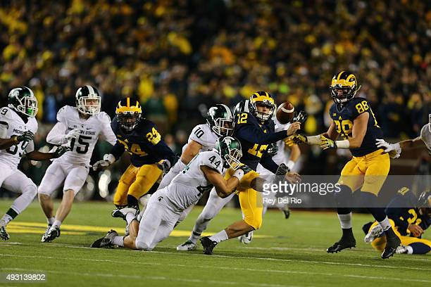 Alex Malzone of the Michigan Wolverines fumbles late in the fourth quarter at Michigan Stadium on October 17, 2015 in East Lansing, Michigan.