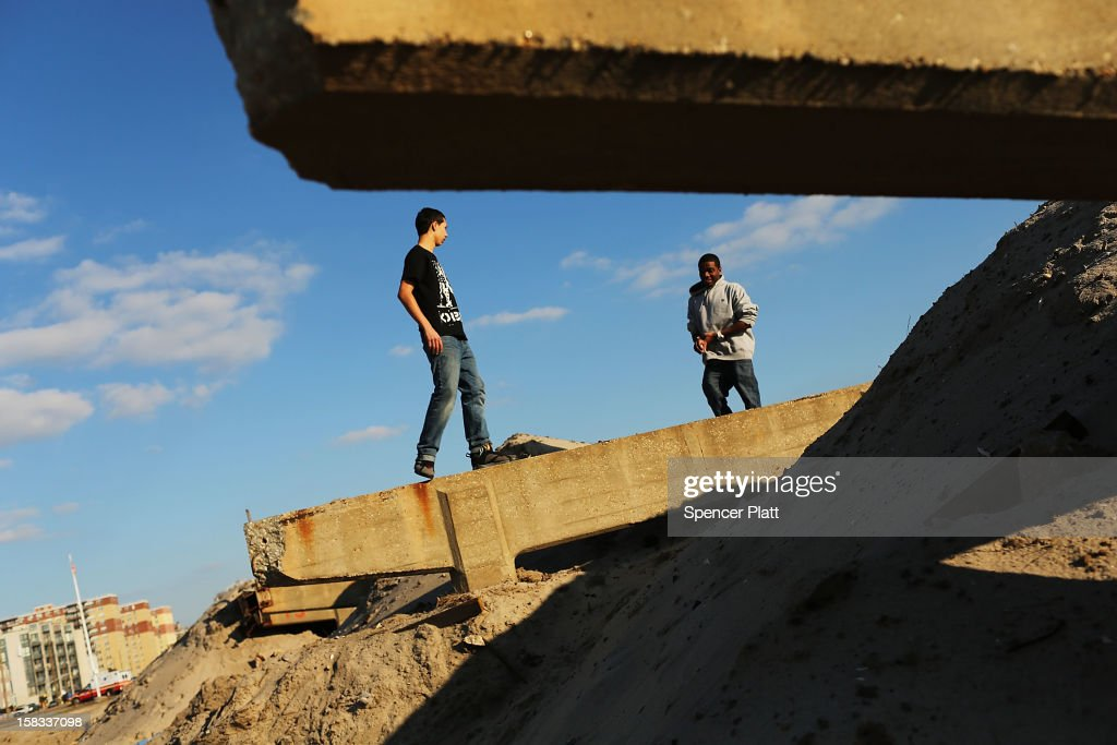 Alex Marin (left) and Bryant Blackshear talk as they practice 'parkour', a sport that embraces the urban landscape as an obstacle course, on the remains of the boardwalk at Rockaway beach on December 13, 2012 in New York City. Much of the Rockaway neighborhood is still suffering the effects of Hurricane Sandy which caused extensive damage to parts of New York, New Jersey and Connecticut. Thousands of Rockaway residents and business owners are still unable to return to their properties while electricity remains sporadic in many neighborhoods.