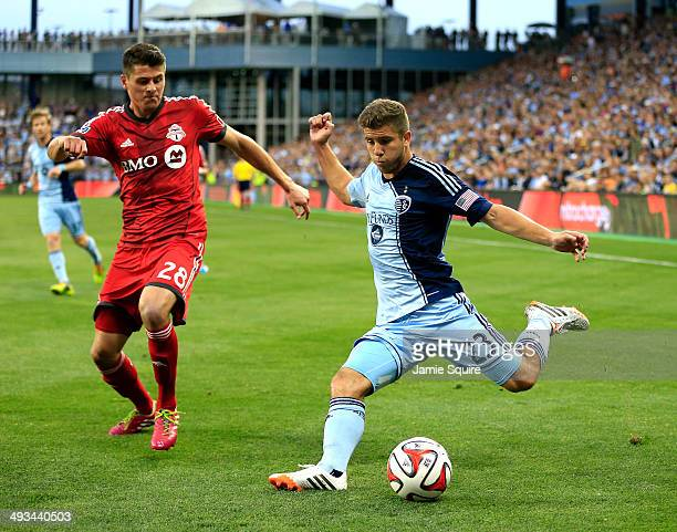 Alex Martinez of Sporting KC crosses the ball as Mark Bloom of Toronto FC defends during the game at Sporting Park on May 23 2014 in Kansas City...