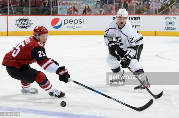 Alex Martinez of the Los Angeles Kings passes the puck as Nick Cousins of the Arizona Coyotes defends during the second period at Gila River Arena on...