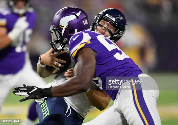 Alex McGough of the Seattle Seahawks is tackled by Antwione Williams of the Minnesota Vikings after scrambling out of the pocket during the fourth...